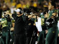 Head coach Chip Kelly of the Oregon Ducks holds his team back seconds before the Ducks defeat the Wisconsin Badgers 45-38 at the 98th Rose Bowl Game on January 2, 2012.
