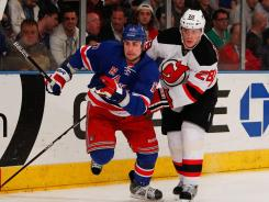 New York left wing Brandon Dubinsky, left, and New Jersey defenseman Anton Volchenkov race to the puck during the Rangers' 4-2 victory over the Devils on Monday night at Madison Square Garden.