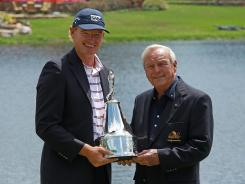 Arnold Palmer presents the trophy to Ernie Els of South Africa after Els won the 2010 Arnold Palmer Invitational.