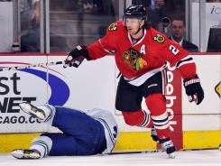 Vancouver winger Daniel Sedin is down on the ice after being elbowed by Chicago defenseman Duncan Keith.