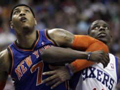 The New York Knicks' Carmelo Anthony, left, and the Philadelphia 76ers' Jrue Holiday struggle for position during the second half in Philadelphia.