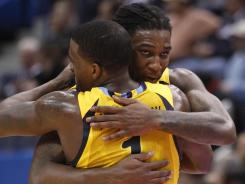 Marquette Golden Eagles forward Jae Crowder and guard Darius Johnson-Odom (1) congratulate each other during the last seconds of play in the second half against Connecticut.