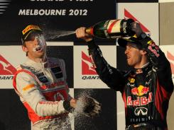 Red Bull driver Sebastian Vettel sprays champagne on McLaren's Jenson Button after Button's win in the Formula One opener at the Australian Grand Prix. Reigning champ Vettel finished second.