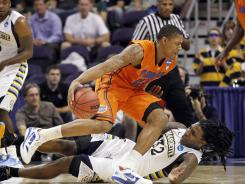 Florida's Bradley Beal moves past Marquette's Jae Crowder (32) as Marquette's Junior Cadougan watches during the first half of Thursday's Sweet 16 game. Beal scored 21 points to lead the Gators.