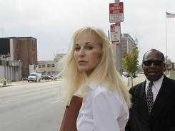 In this Wednesday, July 28, 2010, file photo, Karen Sypher stands with Rev. William Franklin outside the federal courthouse after listening to a day of testimony in her extortion trial in Louisville, Ky. Sypher was convicted of trying to extort millions of dollars from University of Louisville basketball coach Rick Pitino.