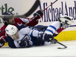 Capitals defenseman Roman Hamrlik, top, fights with Jets right wing Antti Miettinen for the puck during the second period of their game Friday.