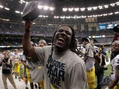 Michigan quarterback Denard Robinson celebrates with teammates after the Wolverines beat Virginia Tech in the Sugar Bowl.