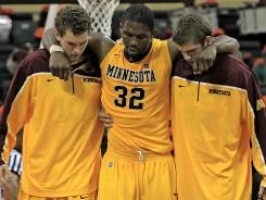 Minnesota forward Trevor Mbakwe (32) gets helped off the court after he hurt his knee in November.