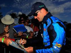 Rubens Barrichello of Brazil signs autographs following practice Saturday.