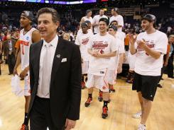 Louisville head coach Rick Pitino, left, is joined by his players on the court following their 72-68 win over Florida in the Elite Eight.