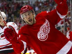 Drew Miller scored the go-ahead goal as the Red Wings rallied by the Hurricanes to snap a six-game slide.
