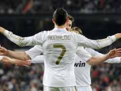 Real Madrid's Cristiano Ronaldo (back) celebrates after scoring a goal against Real Sociedad at the Santiago Bernabeu stadium in Madrid.