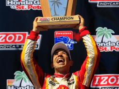 Helio Castroneves of Brazil celebrates winning the Izod IndyCar Series opener in St. Petersburg, Fla.