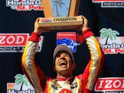 Helio Castroneves of Brazil celebrates winning the Izod IndyCar Series opener in St. Petersburg, Fla.