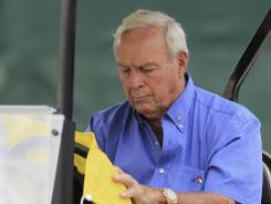 Arnold Palmer signs autographs while sitting in his golf cart during the third round of the Arnold Palmer Invitational on Saturday.