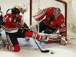 Niklas Hjalmarsson #4 of the Chicago Blackhawks tries to knock the puck away in front of Corey Crawford #50 as Patric Hornqvist #27 of the Nashville Predators reaches in with his stick at the United Center. Crawford made 11 saves.