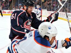 Columbus' Rick Nash, back, is called for boarding after checking Edmonton's Theo Peckham Sunday.