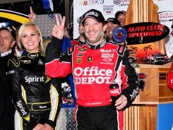 Tony Stewart hold up two fingers — signifying his win total in five races this season — in victory lane after winning the Auto Club 400.