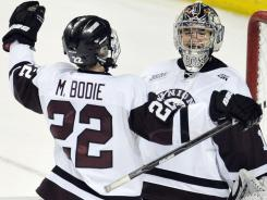 Mat Bodie congratulates Union goalie Tony Grosenick after Union earned its first trip to the Frozen Four.