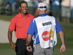Tiger Woods, left, celebrates with caddie Joe LaCava after winning the Arnold Palmer Invitational on Sunday at Bay Hill.