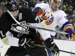 Penguins forward Evgeni Malkin collides with the Islanders' Milan Jurcina as they fight for the puck during their Tuesday night game.