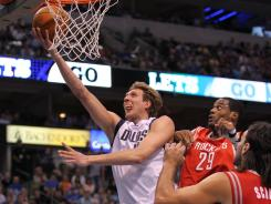 Mavericks forward Dirk Nowitzki drives for a layup past Luis Scola during their game on Tuesday, which the Mavericks won in come-from-behind fashion.