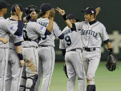 Mariners' Ichiro Suzuki, right, celebrates with teammates after beating the Athletics 3-1 in Tokyo.