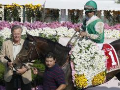 Royal Delta, with jockey Jose Lezcano aboard, won the 2011 Black-Eyed Susan Stakes horse race for trainer Bill Mott, left.