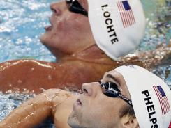 In this July 25, 2011, file photo, Michael Phelps and Ryan Lochte look at the scoreboard after their races in a heat of the men's 200 freestyle event at the FINA Swimming World Championships in Shanghai. The two are expected to race against each other at this week's Indianapolis Grand Prix in the 200 individual medley.