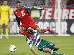 Toronto FC's Ryan Johnson, top, is fouled by Santos Laguna's Marc Crosas during second half action.