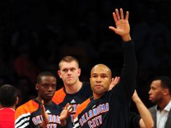 Oklahoma City Thunder guard Derek Fisher waves to fans as he receives applause returning to play against the Los Angeles Lakers at Staples Center Thursday.