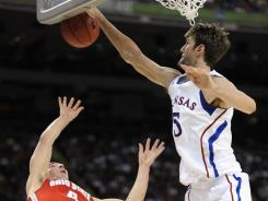 Jayhawks center Jeff Withey blocks the shot of Buckeyes guard Aaron Craft during Saturday's national semifinal game.