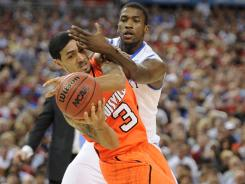 Louisville guard Peyton Siva tries to keep control of the ball in front of Kentucky forward Michael Kidd-Gilchrist.
