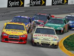 The No. 22 Dodge of A.J. Allmendinger, left, looks to battle eventual winner Ryan Newman in a green-white-checkered finish at Martinsville Speedway.