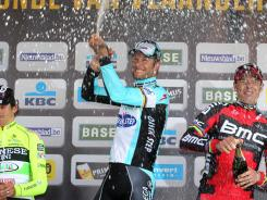Tom Boonen, center, of the Omega Pharma team sprays champaign on the podium after he won the Belgian cycling classic Tour of Flanders, in Oudenaarde, Belgium, on Sunday. Italy's Filippo Pozzato, left, of the Farnese Vini team finished second, Italy's Alessandro Ballan of the BMC Racing team was third.
