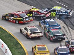 The cars of (from left) Clint Bowyer, Jeff Gordon and Jimmie Johnson crash during the first attempt at an overtime finish Sunday at Martinsville Speedway. Ryan Newman (driving the white car, middle left) dove to the lead after the crash and eventually won the race.