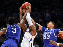 Wildcats forwards Terrence Jones (3) and Anthony Davis (23) battle Kansas forward Thomas Robinson (center) for a loose ball during November's game.