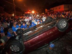 Kentucky fans flip a car on State Street as they celebrate Kentucky's 69-61 win over Louisville on Saturday.