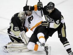 The Flyers' Scott Hartnell is sandwiched by Penguins goalie Marc-Andre Fleury and defenseman Zbynek Michalek during the first period.