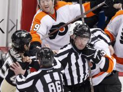 The Flyers' Scott Hartnell (19) reaches for the Penguins' Aaron Asham, left, from the bench, during a third-period fight, as linesmen Brad Lazarowich (86) and Steve Miller, work to separate Asham and the Flyers' Andreas Lilja.