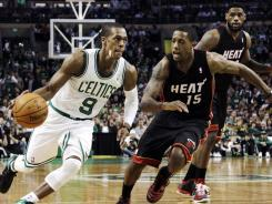 Celtics guard Rajon Rondo drives to the basket against Heat guard Mario Chalmers as forward LeBron James looks on in the second half of their Sunday afternoon game.