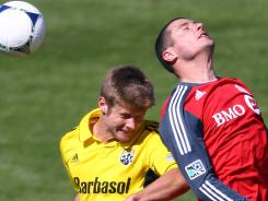 Columbus' Kirk Urso (15) battles for a header against Toronto FC's Danny Koevermans (14) at BMO Field.