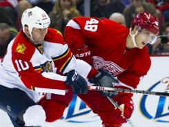 Panthers center John Madden and Red Wings center Cory Emmerton battle for the puck in the third period of their Sunday game.