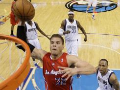 The Los Angeles Clippers' Blake Griffin goes for a dunk as the Dallas Mavericks' Shawn Marion, right, watches the play. Griffin scored 15 points.