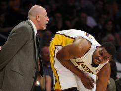 Los Angeles Lakers center Andrew Bynum gets tended to by trainer Gary Vitti in the first quarter of Sunday's win vs. the Golden State Warriors. Bynum left with a sprained ankle.