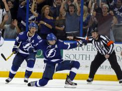 Tampa Bay Lightning's Steven Stamkos, center, celebrates with teammate Martin St. Louis as referee Kelly Sutherland signals Stamkos' goal during the third period against the Washington Capitals in Tampa, Fla. The Lightning won 4-2.