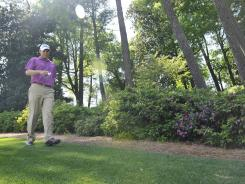 Bill Haas walks along the sixth hole during a practice round Monday. Haas, resplendent in purple, was perhaps the most colorful thing at Augusta National. Because of the warm winter, the flowers and azaleas bloomed too early.