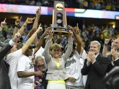 Bears head coach Kim Mulkey raises the championship trophy with her team after beating Notre Dame on Tuesday.