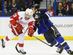 Red Wings center Pavel Datsyuk, left, taking a shot before being checked by Blues defenseman Kevin Shattenkirk, assisted on both of Detroit's goals.