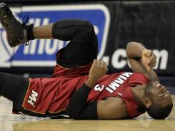 Miami Heat guard Dwayne Wade grimaces after injuring his leg in the fourth quarter the Heat's 117-104 loss to the Denver Nuggets in Denver on Friday, Jan. 13, 2012. His knee reaggrivated, Wade was inactive for Tuesday night's game.